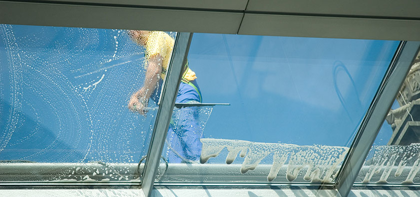 Window Cleaning - man on top of roof cleaning windows